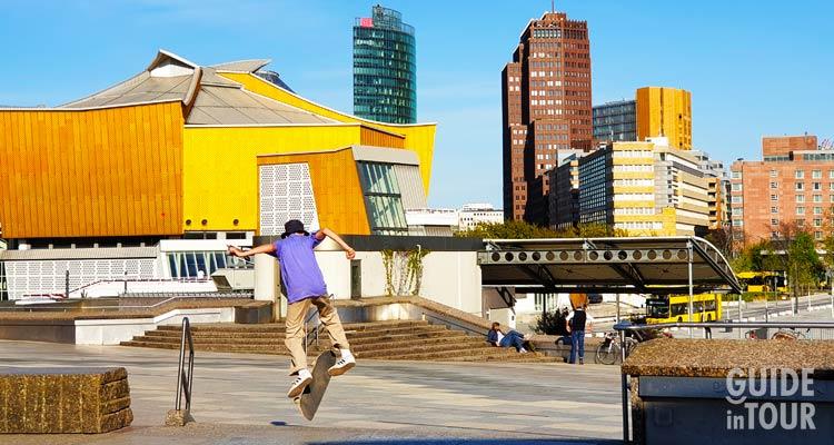 Fra le attrazioni di Berlino non può mancare la Potsdamer Platz. Uin questa foto un gruppo di giovani fanno skate con la piazza più moderna di Berlino in sottofondo.