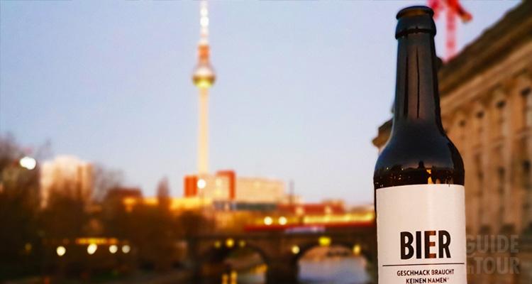 una bottiglia di birra posta sulla spalletta di un ponte di Berlino
