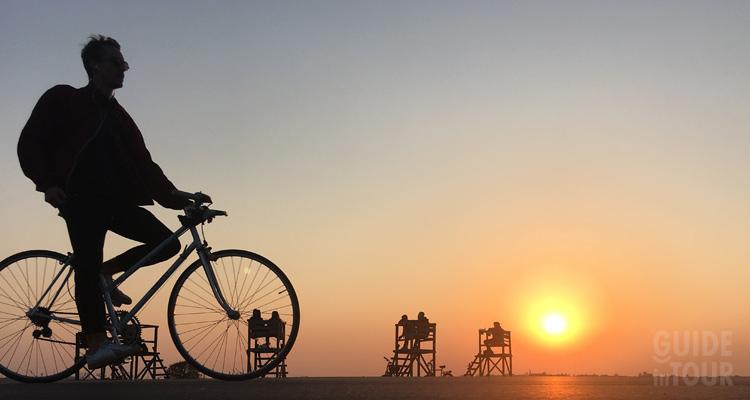 Foto di un ragazzo in bici al tramonto in un parco di Berlino godendo del meteo estivo particolarmente piacevole.