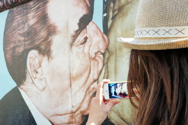 turista fotografando il muro di Berlino durante il tour di berlino durante la guerra fredda