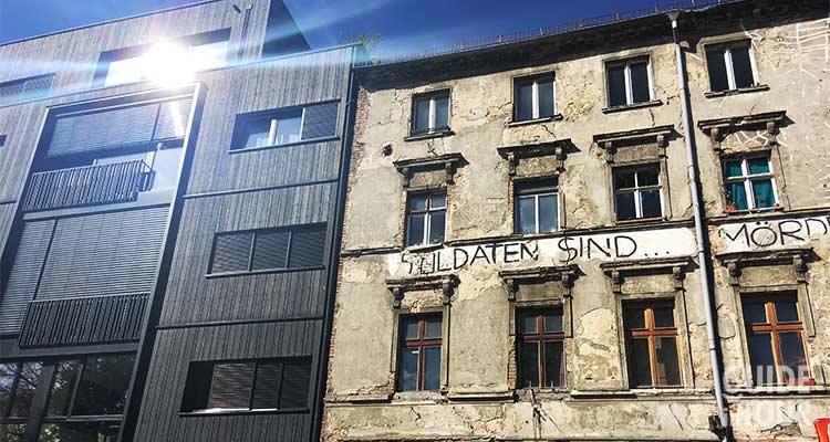 Casa occupata di Berlino Est con un edificio di nuova costruzione a lato.
