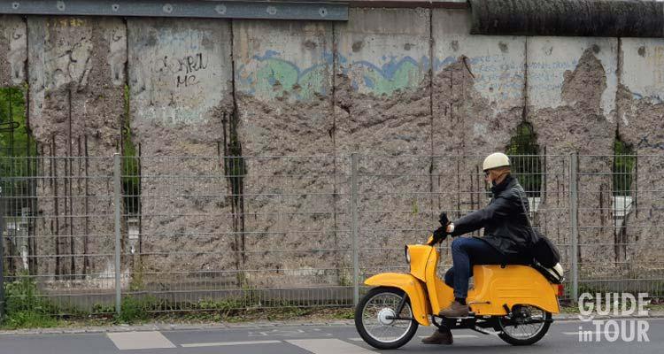 Un persona su una tipica moto della DDR lungo il percorso del Muro di Berlino.