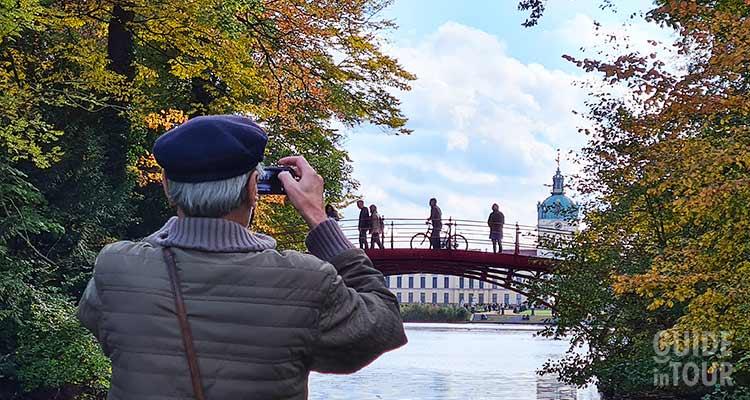 Vista del palazzo di Charlottenburg dal parco dello stesso palazzo. Un uomo si appresta a fotografare il palazzo.