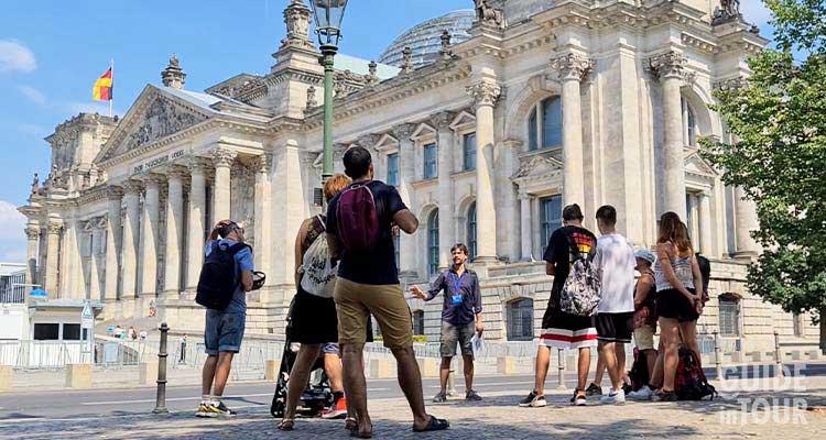 Una guida turistica di Berlino difronte al Palazzo del Reichstag, il Parlamento tedesco.