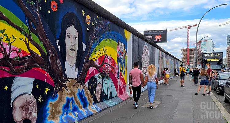Turisti passeggiando alla East Side Gallery, una delle cosa da fare gratis a Berlino.